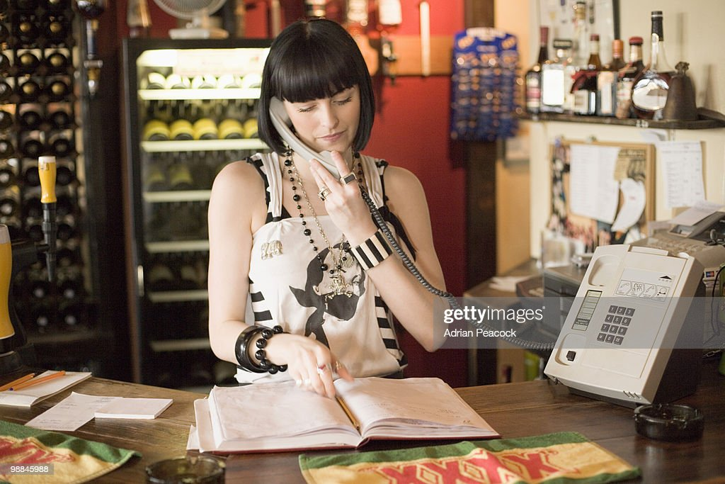 Hostess in cafe using telephone