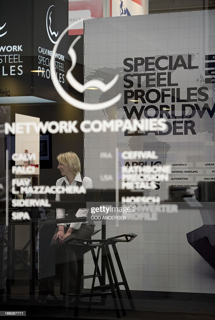 A hostess is seen through the tinted glass of Italian steel company Calvi's booth at the Industrial fair in Hannover in Hanover on April 8, 2013. AFP PHOTO / ODD ANDERSEN