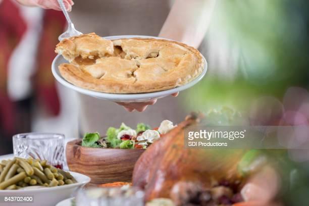 Anfitriona ofrece Navidad cena huéspedes pedazo de pastel