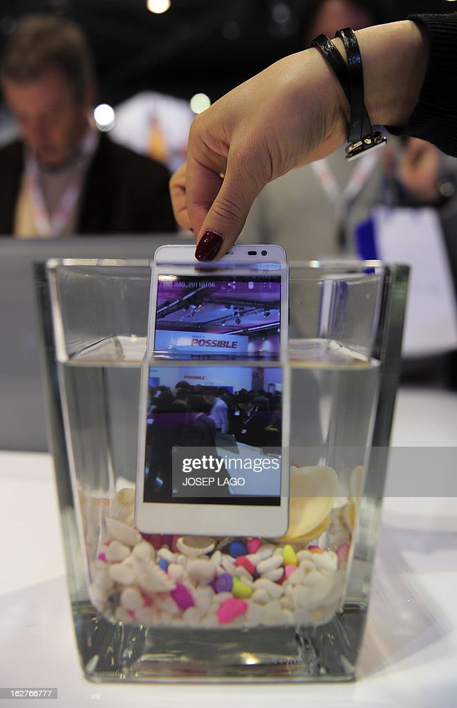 A hostess plunges a new smartphone 'Ascend D2' by Huawei into water at the 2013 Mobile World Congress in Barcelona on February 26, 2013. The 2013 Mobile World Congress, the world's biggest mobile fair, is held from February 25 to 28 in Barcelona. AFP PHOTO / JOSEP LAGO
