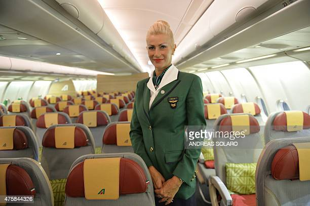 A hostess poses in an aircraft airbus A330200 fom Italy's airline giant Alitalia during a press conference to present the new brand design and the...