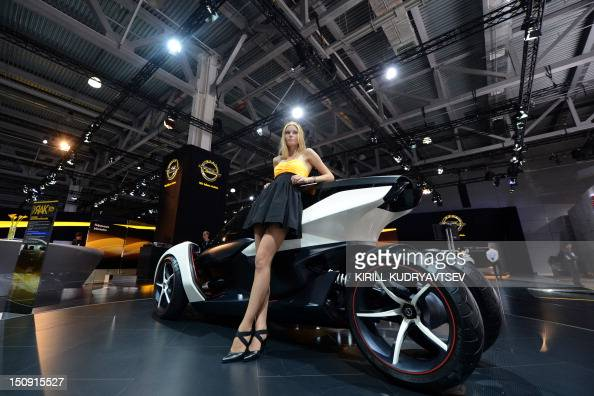 A hostess poses near a Opel/Vauxhall 2seater electric concept car at the Moscow International Automobile Salon on August 29 2012 AFP PHOTO / KIRILL...
