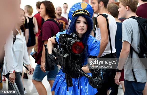A hostess poses with mock gun at the Gamescom fair in Cologne western Germany on August 7 2015 The trade fair for interactive games is running until...