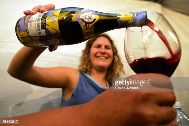 A hostess pours a glass of Beaujolais Nouveau 2005 moments after midnight November 17 2005 in Herzliya central Israel Millions of bottles of this...