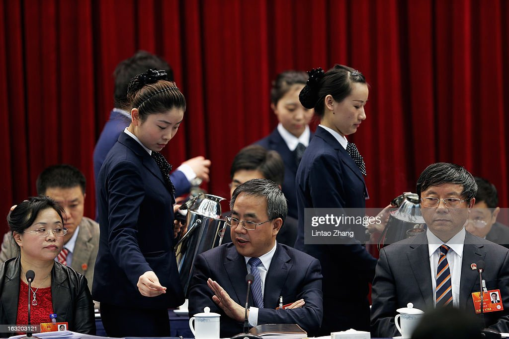 A hostess refreshes the tea cup for Guangdong Communist Party Secretary Hu Chunhua (C) during the Guangdong delegation's group meeting during the annual National People's Congress on March 6, 2013 in Beijing, China.Guangdong's gross domestic product (GDP) reached 5.7 trillion yuan in 2012.