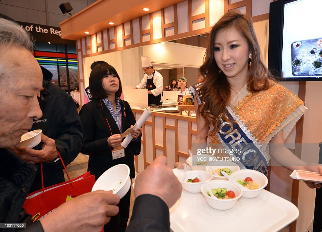 A hostess serves samples of Thai style fried rice to visitors at the annual 'Foodex' food exhibition in Chiba, suburban Tokyo on March 5, 2013. Some 2,300 companies from 66 countries exhibited food, drink, agriculture and marine products at Asia's largest food trade show. AFP PHOTO / Yoshikazu TSUNO