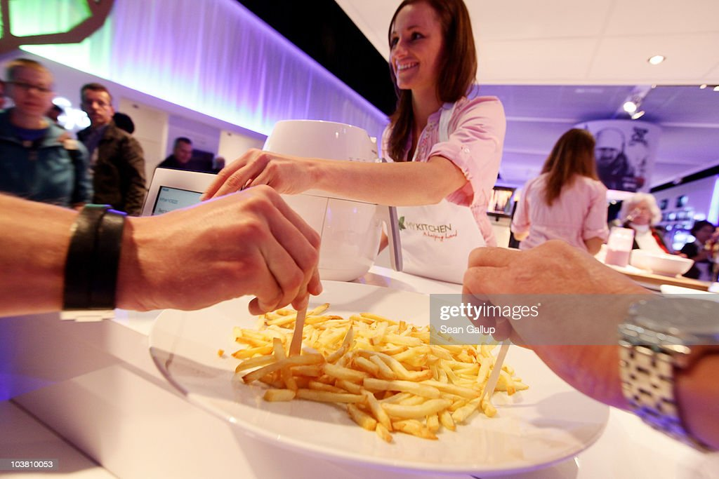 A hostess serves up french fries prepared in the Philips AirFryer, which uses no cooking oil, at the Philips stand at the 2010 IFA technology and consumer electronics trade fair at Messe Berlin on September 3, 2010 in Berlin, Germany. The 2010 IFA will be open to the public from September 3-8.