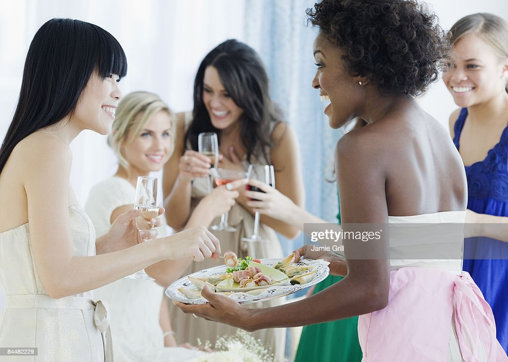 Hostess serving appetizers to her Guests : Stock Photo
