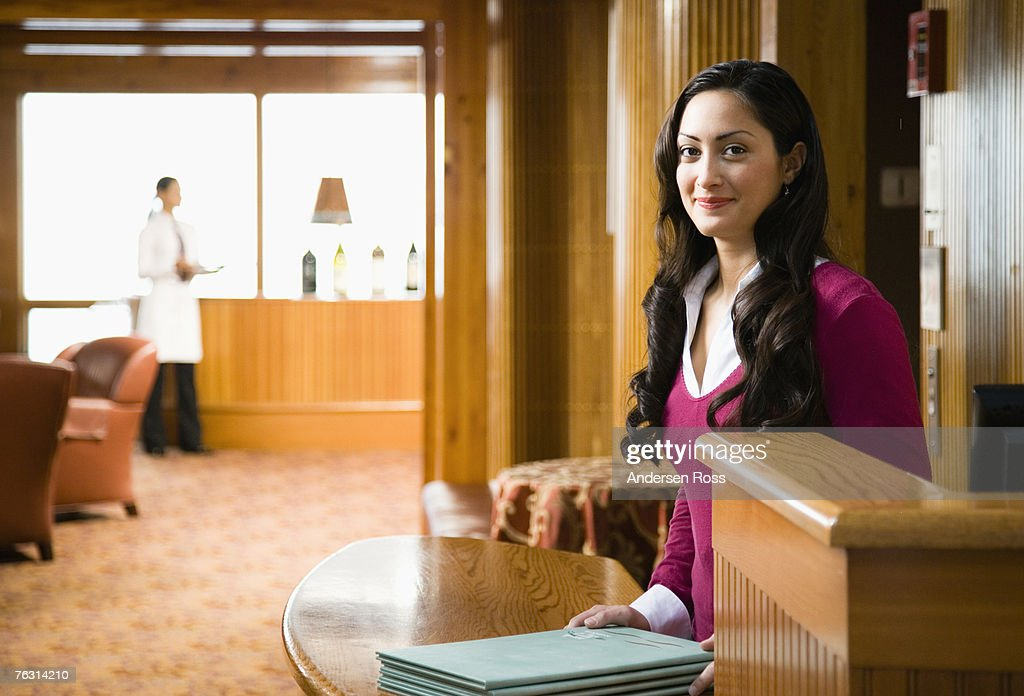 Hostess standing in restaurant with menus, waitress in background