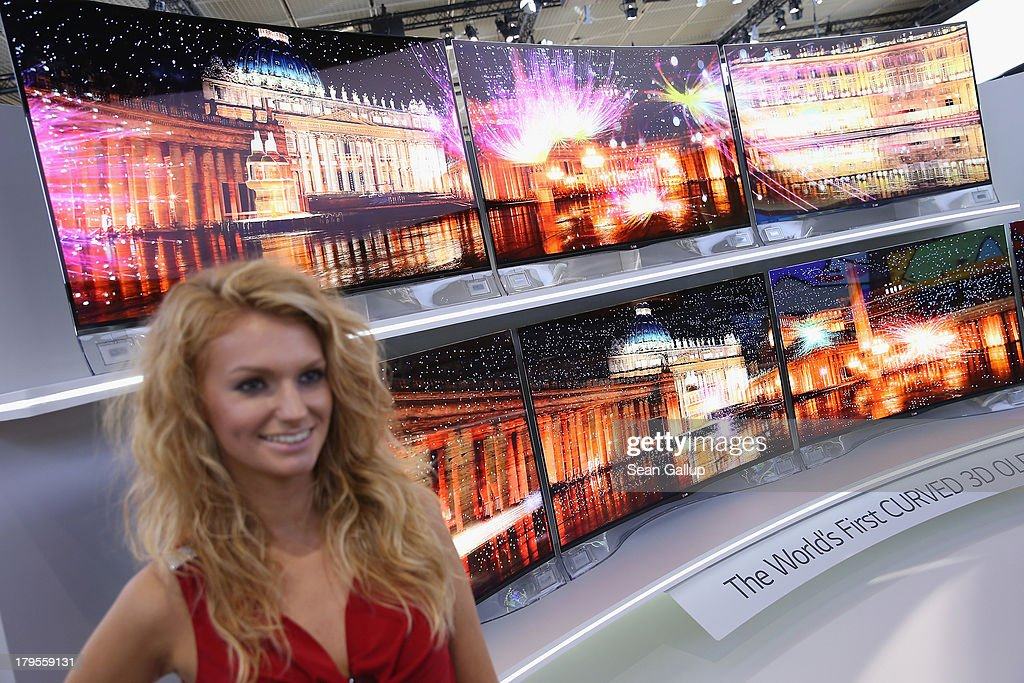 A hostess stands next to curved 3D OLED high-definition flat-screen televisions at the LG stand at the IFA 2013 consumer electronics trade fair on September 5, 2013 in Berlin, Germany. The 2013 IFA will be open to the public from September 6-11.