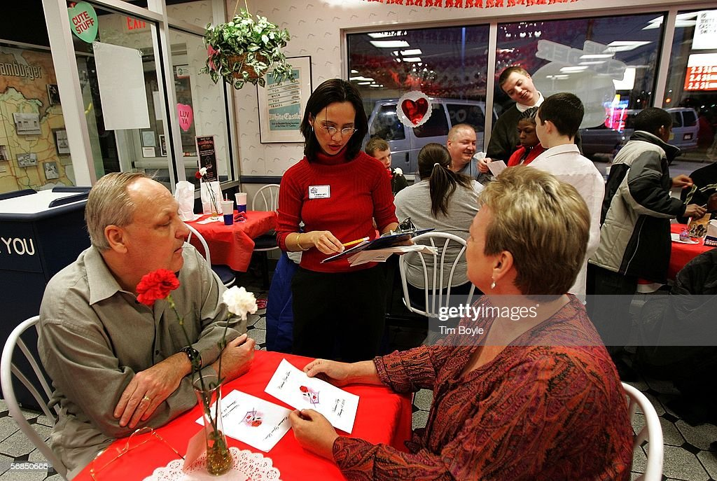 Hostess Yanira Wiley (C) greets customers Tod Rottman and wife Nancy Rottman as they sit for a Valentine's Day dinner at a White Castle restaurant February 14, 2006 in Des Plaines, Illinois. For Valentine's Day, numerous White Castle restaurants nationwide took dinner reservations offering candlelit dining with individual servers as well as hostess seating.