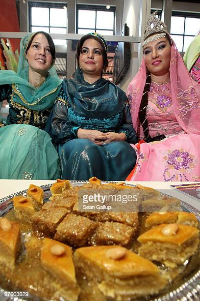 Hostesses dressed in traditional outfits sit at a table of baklava at the Azerbaijan stand at the ITB Berlin travel trade show on March 10 2010 in...