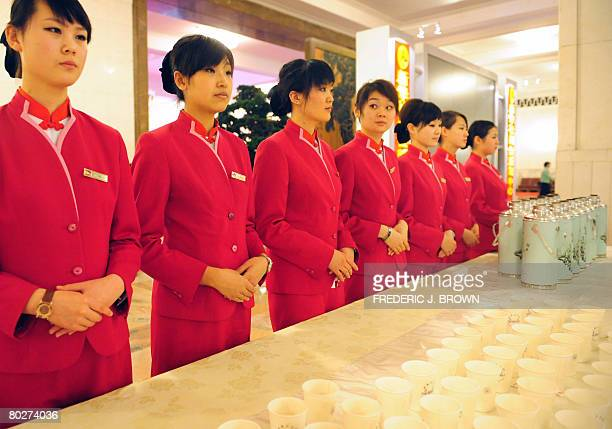 Hostesses inside the Great Hall of the People wait to serve beverages as delegates attend a session of the National People's Congress China's annual...