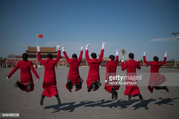 Hostesses jump for a photo during the second plenary session of the National People's Congress China's legislature in front of the Great Hall of the...
