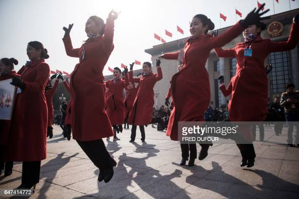Hostesses jump for a picture during the opening session of the Chinese People's Political Consultative Conference in the Great Hall of the People in...