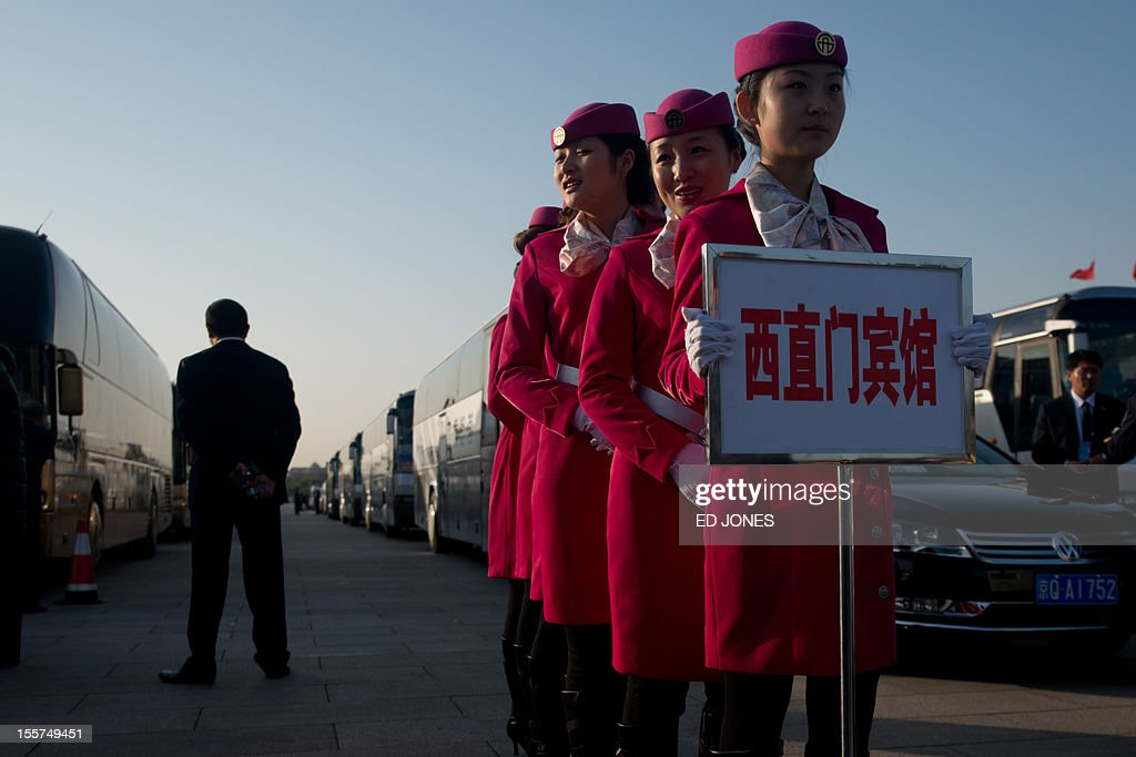 Hostesses line up as they arrive outside the opening session of the Chinese Communist Party's fiveyearly Congress at the Great Hall of the People in...