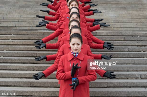 TOPSHOT Hostesses pose for a picture during the opening session of the Chinese People's Political Consultative Conference in the Great Hall of the...
