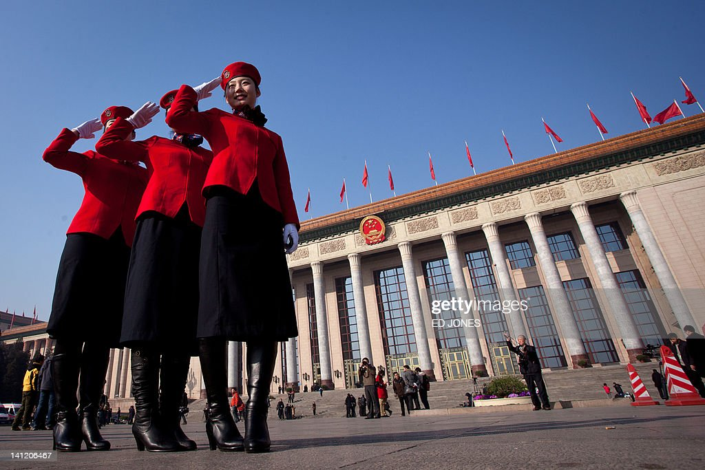 Hostesses pose for photos outside the Great Hall of the People following the last day of the Chinese People's Political Consultative Conference (CPPCC) during the National People's Congress (NPC) in Beijing on March 13, 2012. The 2012 NPC session is the last before a handover of power that begins later this year, and leaders are anxious to ensure the world's second-largest economy grows at a steady pace while keeping a lid on social unrest. AFP PHOTO / Ed Jones