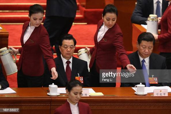Hostesses refresh the cups for Chinese President Hu Jintao and Chinese Communist Party General Secretary Xi Jinping during the opening session of the...