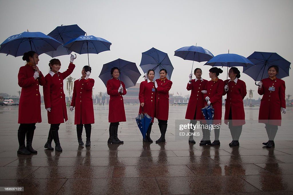 Hostesses stand on Tiananmen Square as they wait for delegates to return during the closing session of the Chinese People's Political Consultative Conference (CPPCC) at the Great Hall of the People in Beijing on March 12, 2013. Thousands of delegates from across China met this week to seal a power transfer to new leaders whose first months running the Communist Party have pumped up expectations with a deluge of propaganda. AFP PHOTO / Ed Jones