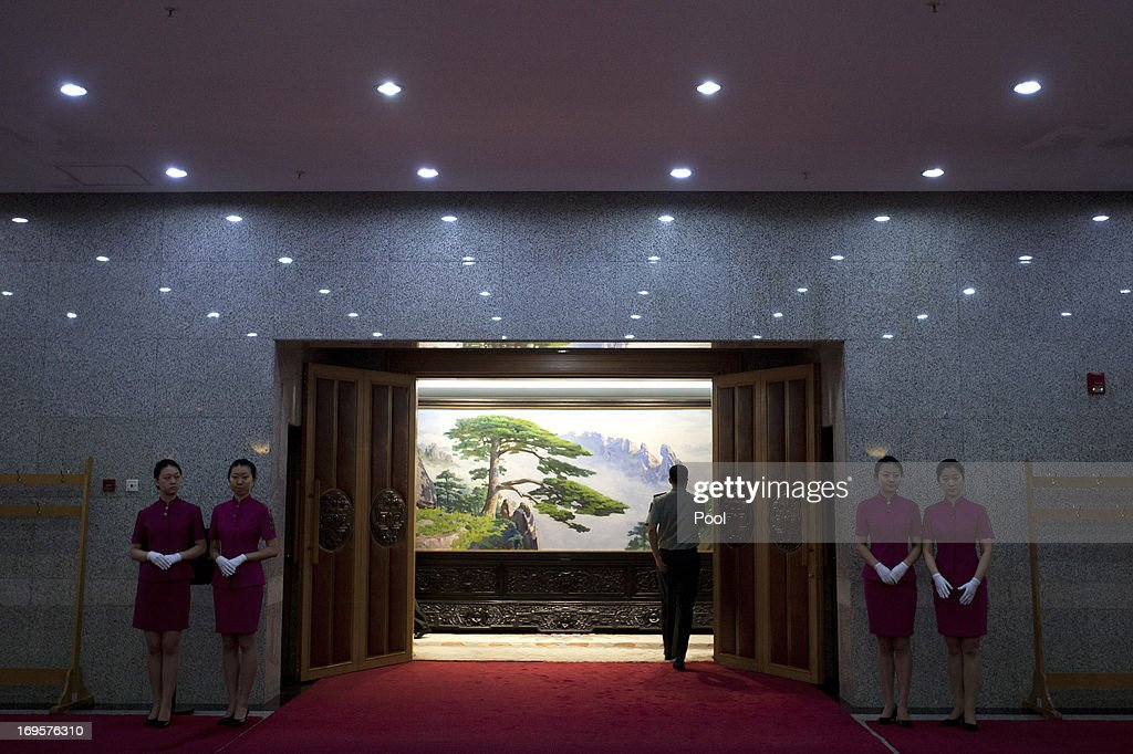 Hostesses stand outside a meeting room while a Chinese People's Liberation Army (PLA) officer enters the room, before a meeting between U.S. National Security Adviser Tom Donilon and Vice Chairman of China's Central Military Commission, General Fan Changlong at the Bayi Building, headquarters of Chinese Defense Ministry, on May 28, 2013 in Beijing, China.