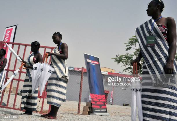 Hostesses stand outside a new movie theatre which runs on solar power during its inauguration in Ouagadougou on February 24 on the eve of the opening...