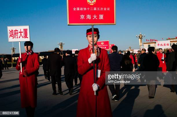 CORRECTION Hostesses stand with boards to help delegates find their way at the end of the Chinese People's Political Consultative Conference plenary...