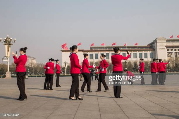 Hostesses take pictures in Tiananmen Square during the opening session of the Chinese People's Political Consultative Conference in the Great Hall of...