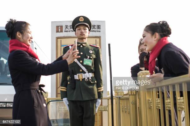 TOPSHOT Hostesses take pictures next to a paramilitary guard during the opening session of the Chinese People's Political Consultative Conference in...