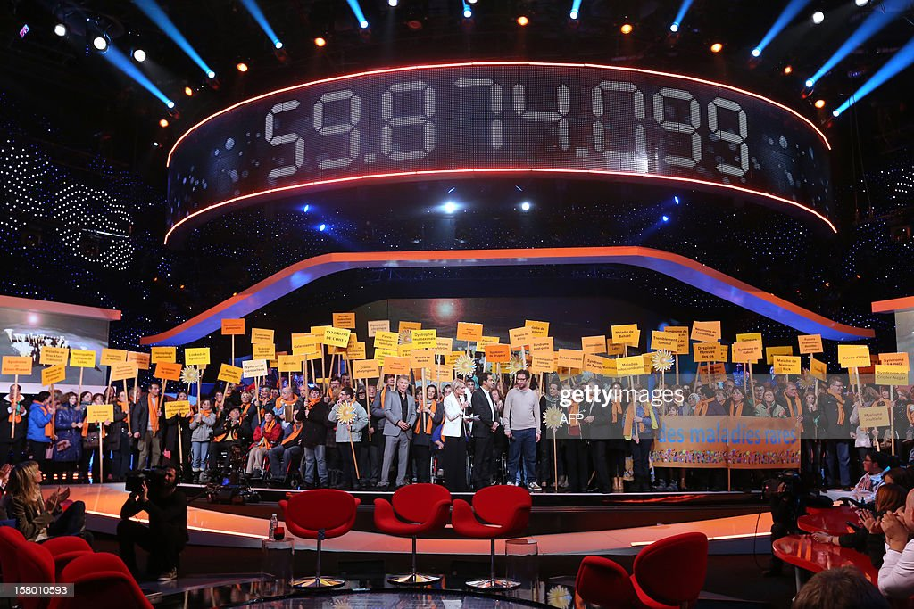 TV hosts and participants stand under the counter reading an amount of 95,874,099 euros during of the 26th Telethon, France's biggest annual fund-raising event during 30 hours of live television transmission, on December 8, 2012 in Saint-Denis, north of Paris. The event, organised by (French Association Against Myopathy (AFM) aims at collecting funds for research on genetic diseases such as myopathy, a neuromuscular disease.
