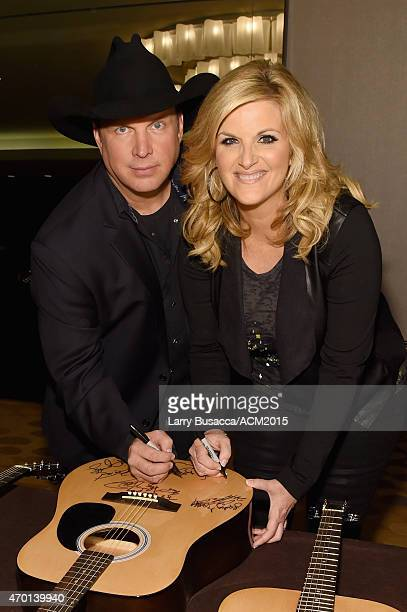 Hosts Garth Brooks and Trisha Yearwood autograph a guitar at the ACM Lifting Lives Gala at the Omni Hotel on April 17 2015 in Dallas Texas