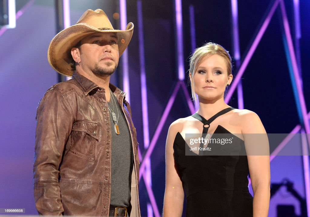 Hosts <a gi-track='captionPersonalityLinkClicked' href=/galleries/search?phrase=Jason+Aldean&family=editorial&specificpeople=619221 ng-click='$event.stopPropagation()'>Jason Aldean</a> and <a gi-track='captionPersonalityLinkClicked' href=/galleries/search?phrase=Kristen+Bell&family=editorial&specificpeople=194764 ng-click='$event.stopPropagation()'>Kristen Bell</a> speak onstage at the 2013 CMT Music Awards at the Bridgestone Arena on June 5, 2013 in Nashville, Tennessee.