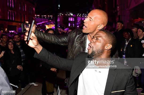 Hosts Kevin Hart and Dwayne Johnson take selfies backstage at the 2016 MTV Movie Awards at Warner Bros Studios on April 9 2016 in Burbank California...