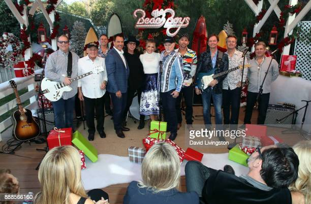 Hosts Mark Steines and Debbie Matenopoulos pose with singer Mike Love and other members of The Beach Boys at Hallmark's 'Home Family' at Universal...