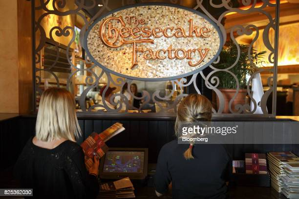 Hosts stack menus at the entrance to a Cheesecake Factory Inc restaurant in the Canoga Park neighborhood of Los Angeles California US on Tuesday Aug...
