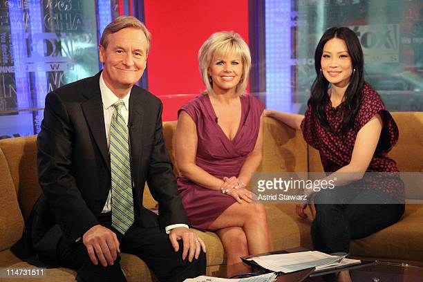 Hosts Steve Doocy and Gretchen Carlson pose for photos with actress Lucy Liu during a taping of FOX Friends at FOX Studios on May 26 2011 in New York...