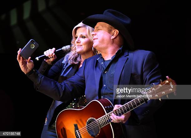 Hosts Trisha Yearwood and Garth Brooks pose for a selfie photo while performing onstage during the ACM Lifting Lives Gala at the Omni Hotel on April...