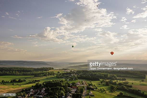 Hot air ballon above green fields and villages