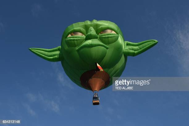 TOPSHOT A hot air ballon in the likeness of Star Wars film character Yoda takes flight during the annual International Hot Air Balloon Festival at...