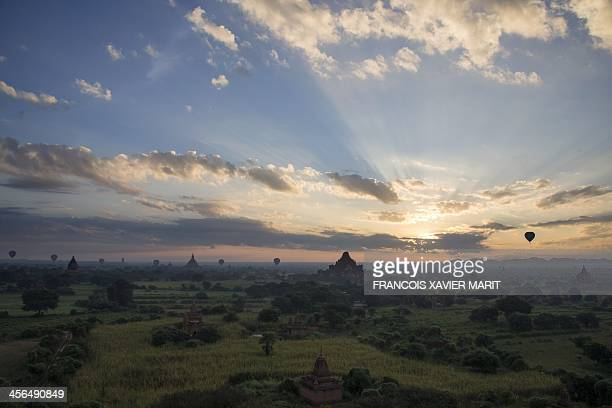 Hot air ballons fly over temples while the sun rises on December 1 2013 in Bagan AFP PHOTO / FRANCOIS XAVIER MARIT