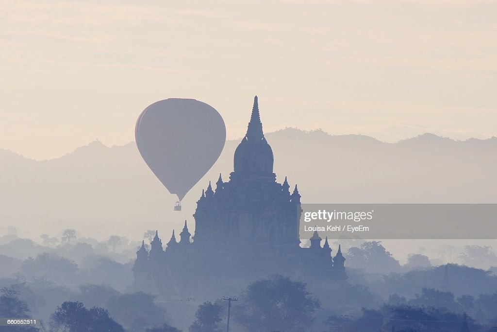 Hot Air Balloon And Temple Against Sky On Sunny Day