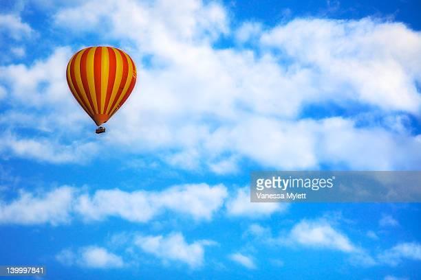 Hot air balloon drifting in blue sky