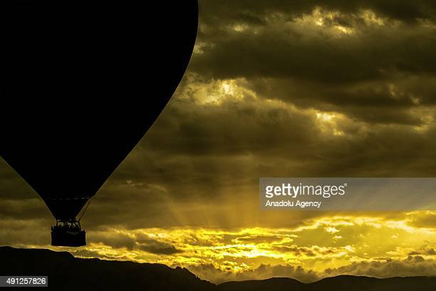 A hot air balloon flies above Albuquerque as the sun rises behind the Sandia Mountains during the Albuquerque International Balloon Fiesta in New...