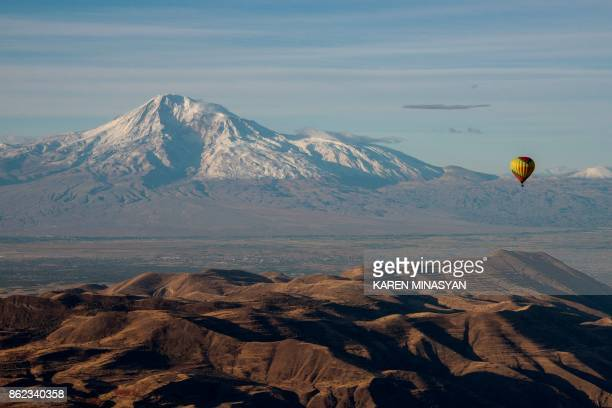 A hot air balloon flies on October 17 2017 during the balloon festival in honor of the 2799th birthday of the Armenian capital as Mount Ararat is...
