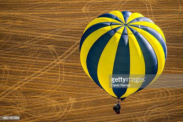 A hot air balloon flies over crops during an early flight as part of the European Balloon Festival on July 10 2015 in Igualada Spain Now is the 19th...