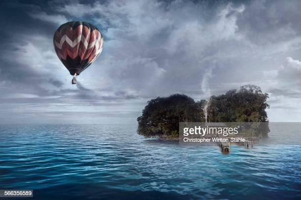 Hot air balloon floating over house on tropical island