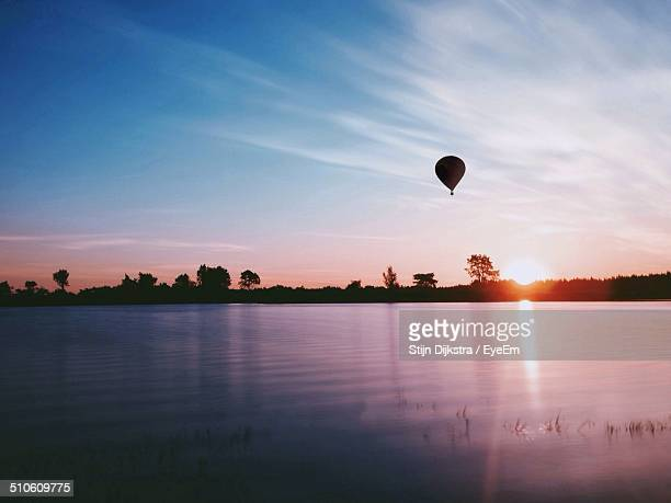 Hot air balloon flying above lake at sunset