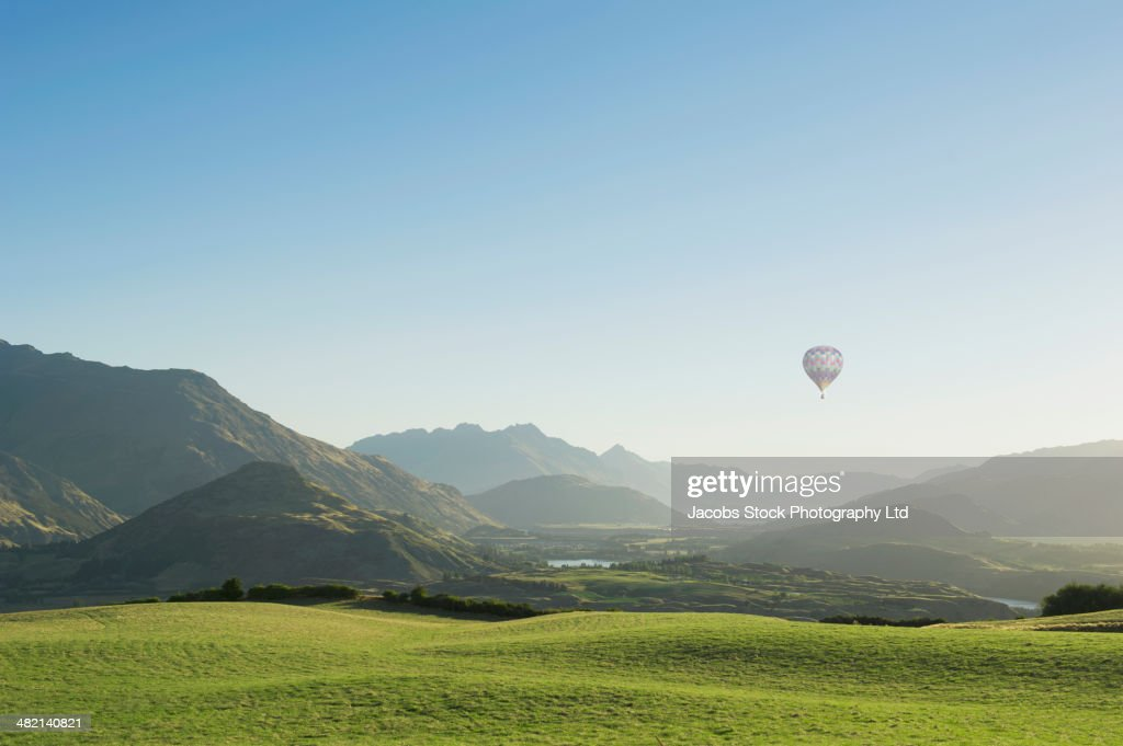 Hot air balloon flying above rolling landscape : Stock Photo