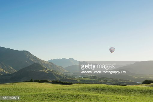 Hot air balloon flying above rolling landscape