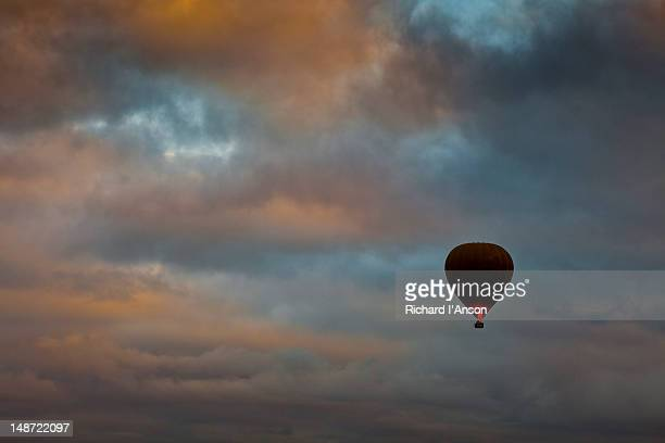 Hot air balloon flying over city at sunrise.